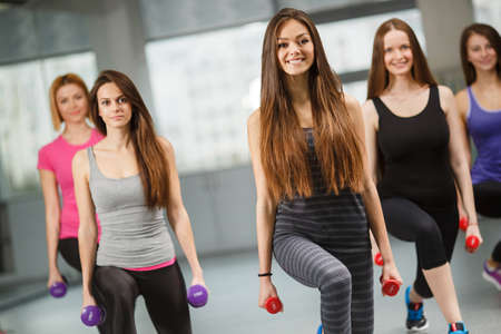 gym equipment: Slender women with beautiful shapes and flowing hair, dressed in sports clothes, carry out a workout in the fitness centre, gym, light grey, perform exercises with dumbbells with alternate lunges right and left leg Stock Photo
