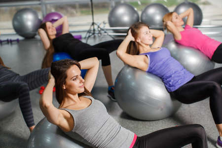 steel balls: Beautiful young women of a sport constitution, with a flowing hair, are dressed in clothes sportswear, carry out training in the fitness center in a light gym of gray color, carry out exercises with big gymnastic balls of blue and steel color