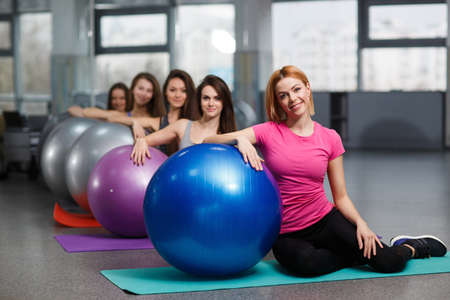 Beautiful young women of a sport constitution, with a flowing hair, are dressed in clothes sportswear, carry out training in the fitness center in a light gym of gray color, carry out exercises with big gymnastic balls of blue and steel color