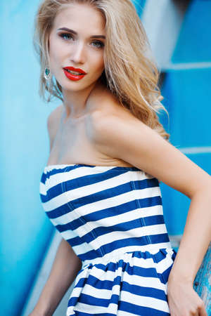 nude blond girl: Attractive young woman with long blonde hair and gray eyes, wearing a long white and blue striped dress, makeup and beautiful smile, posing on a blue background, sitting on the step, summer portrait outdoors