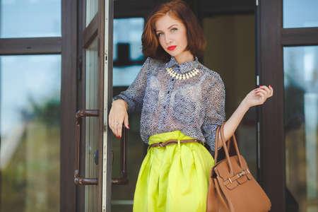 La mujer hermosa con un pelo nutbrown y un peinado elegante, ojos grises y la barra de labios roja vestida con una falda de color de limón y una blusa gris lleva un collar blanco, esmalte de uñas rojo, posa con una bolsa marrón en una entrada de un supermercado