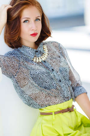 gray eyes: Fashion woman with brown hair and stylish hair, gray eyes and red lipstick, dressed in lemon-colored skirt and gray blouse, wears a white necklace, red nail Polish, posing on the street in the city in the summer