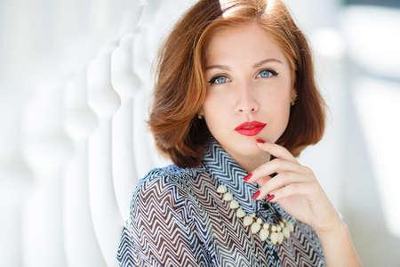 Fashion Frau mit braunen Haaren und stilvolle Haare, graue Augen und roten Lippenstift, gekleidet in zitronenfarbenen Rock und graue Bluse, trägt eine weiße Halskette, Roter Nagellack, auf der Straße im Sommer in der Stadt aufwirft