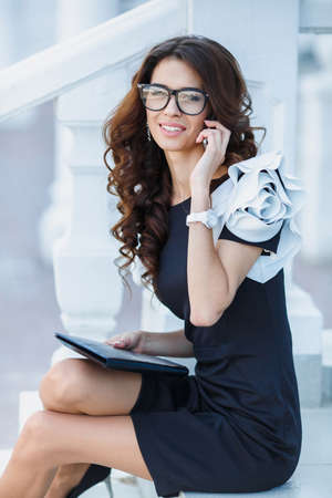 topicality: Cute business woman brunette with long curly hair, dressed in a black dress with white sleeves, wearing glasses, sitting on stairs near white railings, works with a tablet PC and talking on mobile phone outdoors Stock Photo
