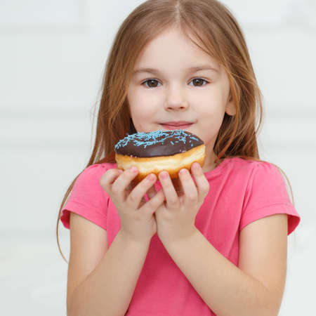 snack: Adorable little girl with a chocolate donut.Adorable little girl, a brunette with long straight hair and brown eyes, dressed in a pink summer dress, holding a fresh donut with chocolate glaze, posing on grey background