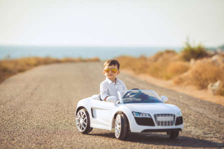 The young driver, a boy with brunette short hair, mirrored sun glasses yellow, in white shirt posing on a mountain road against the sea and clear sky, sitting in a posh toy car white color in the fresh summer air