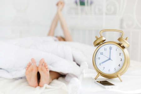 punctual: mujer pelirroja hermosa joven con el pelo largo y rizado, vestido con un camisón blanco dormido en una almohada suave en una cama blanca en el dormitorio brillante en una gran cama blanca, un gran reloj de alarma muestra de color oro