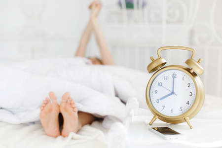 Young beautiful redhead woman with long curly hair, dressed in a white nightshirt asleep on a soft pillow in a white bed in bright bedroom on a large white bed, a big alarm clock Golden color shows Stock Photo