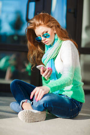 knitted jacket: The young beautiful woman with the red curling long hair, an easy make-up and pink nail varnish, is dressed in a knitted jacket of white-green color, on a neck carries a blue-green easy scarf, wears blue jeans, reads a SMS message on the mobile phone