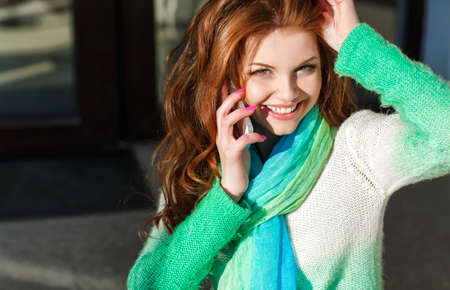 autumn color: Young beautiful woman with red curly long hair and green eyes, light makeup and pink nail Polish, dressed in a knitted sweater white-green color, the neck is blue-green light scarf, talking on a cell phone in the city autumn Stock Photo