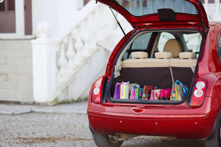 Open the trunk of the car with bags of purchases.The red car is a hatchback, the seats beige color, stands alone near the entrance to the shopping centre with an open trunk lid, filled with colored paper bags for shopping ahead Stock Photo