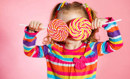 Funny little girl with long, curly red hair, bright ribbons tied into two tails, a sweet smile, wearing a bright dress with a red bow on the chest, posing in Studio on pink background holding two big colorful Lollipop Standard-Bild
