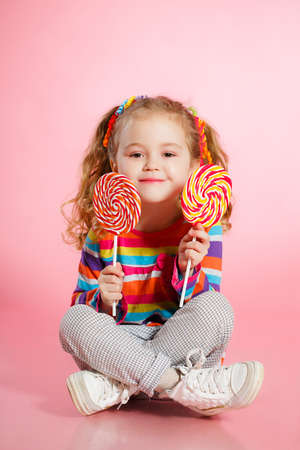 piruleta: Ni�a divertida con el pelo rojo largo, rizado, cintas brillantes atado en dos colas, una sonrisa dulce, con un vestido brillante con un lazo rojo en el pecho, que presenta en estudio en el fondo de color rosa la celebraci�n de dos grandes Lollipop colorido