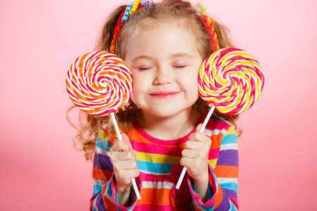 lollipop: Funny little girl with long, curly red hair, bright ribbons tied into two tails, a sweet smile, wearing a bright dress with a red bow on the chest, posing in Studio on pink background holding two big colorful Lollipop Stock Photo
