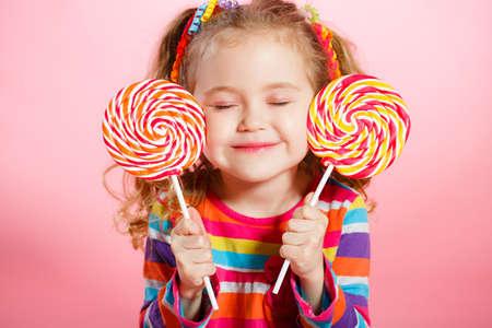 Niña divertida con el pelo rojo largo, rizado, cintas brillantes atado en dos colas, una sonrisa dulce, con un vestido brillante con un lazo rojo en el pecho, que presenta en estudio en el fondo de color rosa la celebración de dos grandes Lollipop colorido Foto de archivo