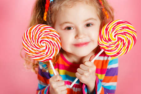 paleta de caramelo: Niña divertida con el pelo rojo largo, rizado, cintas brillantes atado en dos colas, una sonrisa dulce, con un vestido brillante con un lazo rojo en el pecho, que presenta en estudio en el fondo de color rosa la celebración de dos grandes Lollipop colorido