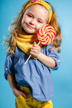 lollipop: Funny little girl with long, curly red hair, with a yellow handkerchief around his neck, a sweet smile, is dressed in a blue shirt and yellow pants, posing in Studio standing against a blue background, holding a large, round, colourful Lollipop