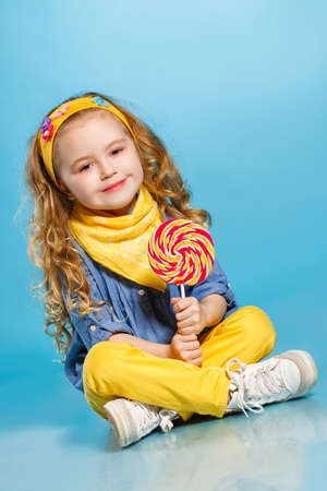 Funny little girl with long, curly red hair, with a yellow handkerchief around his neck, a sweet smile, is dressed in a blue shirt and yellow pants, posing in Studio sitting on the floor on a blue background holding a large, round, colourful Lollipop