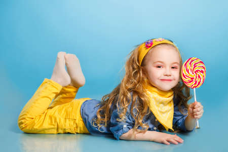 Funny little girl with long, curly red hair, with a yellow handkerchief around his neck, a sweet smile, is dressed in a blue shirt and yellow pants, posing in Studio laying on the floor on a blue background holding a large, round, colourful Lollipop Stock Photo