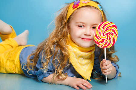 lollipop: Funny little girl with long, curly red hair, with a yellow handkerchief around his neck, a sweet smile, is dressed in a blue shirt and yellow pants, posing in Studio laying on the floor on a blue background holding a large, round, colourful Lollipop Stock Photo