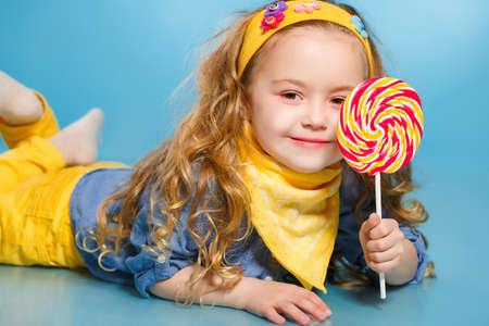 paleta de caramelo: Ni�a divertida con el pelo rojo largo, rizado, con un pa�uelo amarillo alrededor de su cuello, una sonrisa dulce, est� vestido con una camisa azul y pantalones amarillos, que presenta en estudio tirado en el suelo sobre un fondo azul con un grande, redondo, colorido Chupete