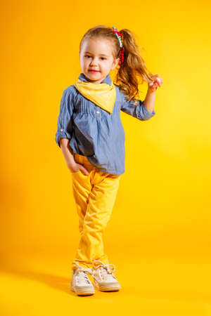 Portrait of a cute small girl, brunette with brown eyes and long curly hair, tied with a ribbon, a shirt of blue-gray and yellow handkerchief around his neck, yellow pants, posing in Studio on a bright yellow background Stock Photo