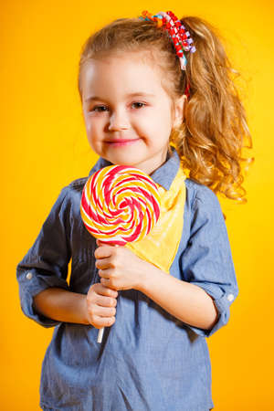 lollipop: little girl with long, curly red hair, with a yellow handkerchief around his neck, a sweet smile, is dressed in a blue shirt and yellow pants, posing in Studio standing against a bright yellow background, holding a large, round, colourful Lollipop Stock Photo
