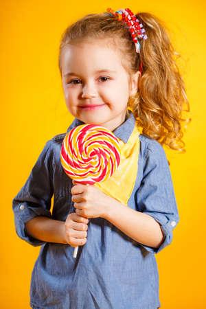 paleta de caramelo: niña con el pelo largo de color rojo, rizado, con un pañuelo amarillo alrededor de su cuello, una sonrisa dulce, está vestido con una camisa azul y pantalones amarillos, posando en el estudio de pie sobre un fondo de color amarillo brillante, con un grande, redondo, Lollipop colorido