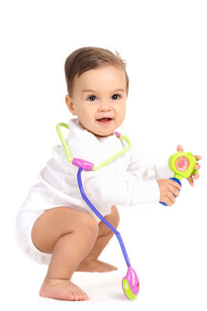 paediatrics: Portrait of a curious little boy, brunette with brown eyes and short hair, dressed in a white shirt and a white diaper, barefoot posing in Studio, sitting on a white background, smiling mouth open, plays with a toy stethoscope