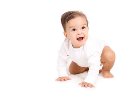 Adorable baby isolated on white.Portrait of a curious little boy, brunette with brown eyes and short hair, dressed in a white shirt and a white diaper, barefoot posing in Studio, sitting on a white background, smiling mouth open Stock Photo