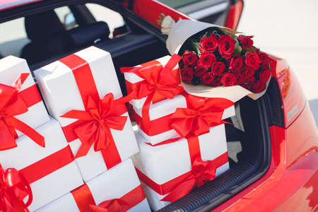 neatly stacked: Gift boxes in a luggage carrier of the red car.White boxes with gifts tied with red ribbons with large red bows and a huge bouquet of red roses, neatly stacked in the open trunk of the big red car, the concept of celebration and love