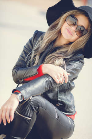 long pants: Portrait of a young woman with a beautiful smile, blonde long hair, dressed in a black leather jacket, black hat with large brim and black leather pants, wears dark sun glasses, sitting alone outside on a Sunny day