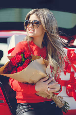 sexy blonde woman: The young woman, the blonde with a thick long hair, in sun glasses, a red t-shirt and black leather trousers, with a big bouquet of scarlet roses poses near the red car loaded by gift boxes