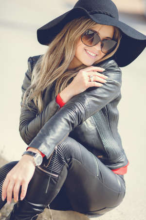 Portrait of a young woman with a beautiful smile, blonde long hair, dressed in a black leather jacket, black hat with large brim and black leather pants, wears dark sun glasses, sitting alone outside on a Sunny day