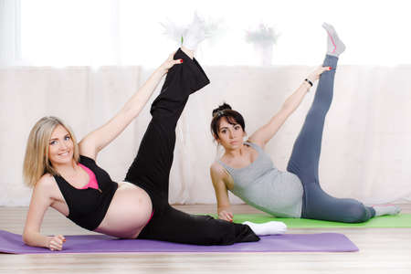 sports attire: Pregnant cute women, blonde and brunette, dressed in sports attire, perform stretching exercises in prenatal yoga to strengthen the muscles that hold classes in the gym bright in the daytime