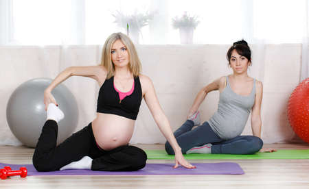 prenatal: Pregnant cute women, blonde and brunette, dressed in sports attire, perform stretching exercises in prenatal yoga to strengthen the muscles that hold classes in the gym bright in the daytime