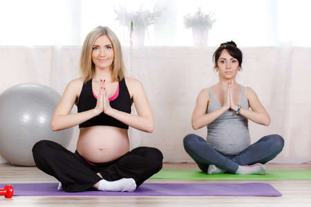 prenatal: Two cute pregnant woman, blond and brunette, dressed in sportswear clothing, carry a soothing exercise in prenatal yoga classes in the gym, sitting in lotus posture, breathing and meditation Stock Photo