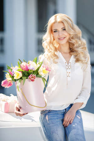 gray eyes: Young beautiful woman with long blonde curly hair and gray eyes, light makeup and a beautiful smile, dressed in a white shirt posing with a bouquet of multicolored tulips near the white car in the summer in the city
