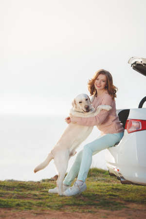 faithful: A beautiful young woman, brunette with blue eyes and curly hair, dressed in a white jacket and light trousers, spends time on a rocky beach in the spring with his faithful friend, the dog breed white Labrador