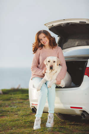 trusting: A beautiful young woman, brunette with blue eyes and curly hair, dressed in a white jacket and light trousers, spends time on a rocky beach in the spring with his faithful friend, the dog breed white Labrador