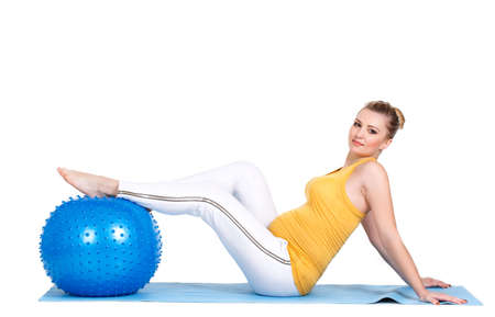 pleasantness: The young pregnant woman, the blonde with brown eyes, is dressed in a yellow jersey and white sports pants, carries out a set of exercises for pregnant women with a big gymnastic ball of blue color in studio on a white background