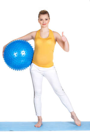 waiting posture: The young pregnant woman, the blonde with brown eyes, is dressed in a yellow jersey and white sports pants, carries out a set of exercises for pregnant women with a big gymnastic ball of blue color in studio on a white background