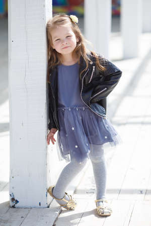 straight jacket: Portrait of a little girl with pale straight hair, wearing a leather jacket of black color and gray-blue gown, in her hair wears a white flower, posing to photographer on a Sunny day in the city outdoors in the spring