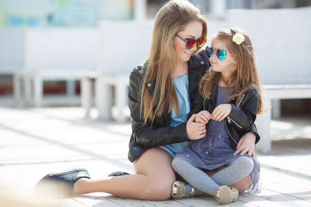 Happy mother and her little daughter four years of age, both blonde with straight long hair, both dressed in fashionable leather jackets in black and a light summer dress, wearing dark sun glasses, spend time together outside in the spring