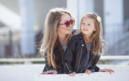 Happy mother and her little daughter four years of age, both blonde with straight long hair, both dressed in fashionable leather jackets in black and a light summer dress, moms got dark sun glasses, spend time together outside in the spring