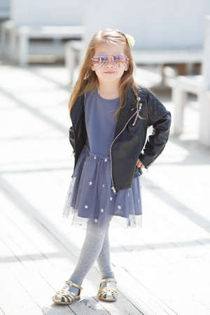 straight jacket: Portrait of a little girl with blond straight hair, big sun glasses, wearing a leather jacket of black color and gray-blue gown, in her hair wears a white flower in the city posing outdoors in the spring