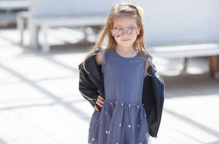 Portrait of a little girl with blond straight hair, big sun glasses, wearing a leather jacket of black color and gray-blue gown, in her hair wears a white flower in the city posing outdoors in the spring