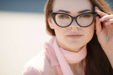 black rimmed: Young beautiful woman brunette with long straight hair and brown eyes, dressed in a pink blouse and pink scarf around his neck, wears black rimmed glasses, posing for the photographer in the summer outdoors