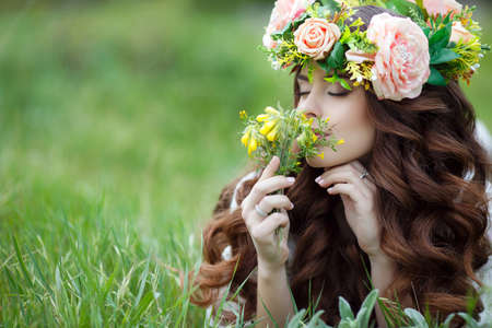 gray eyes: Spring portrait of a beautiful woman in a wreath of flowers, long curly red hair, gray eyes, light makeup and a beautiful smile, dressed in a white summer dress, lying on the soft green grass outdoors in spring