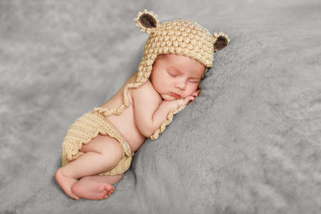Peaceful sleep of a newborn baby. Newborn baby brown knitted cap with black ears, sleeping sweetly on a soft gray blanket, tucked under his legs and put the handle under my cheek